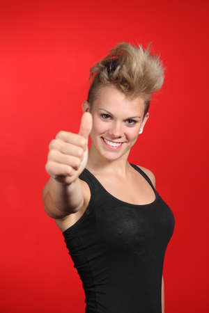 Close up of a fashion teenager girl with thumb up in a red background photo