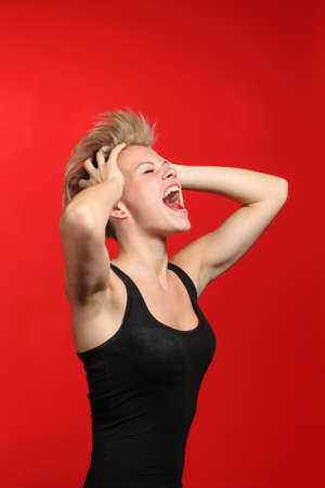 Fashion woman shouting with her hands on the head and opened mouth on a red background              photo