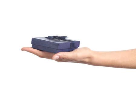 dar un regalo: Mujer mano con la palma hacia arriba con una caja de regalo azul aislado en un fondo blanco Foto de archivo