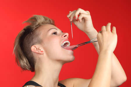 girl tongue: Woman piercing the tongue herself on a red background