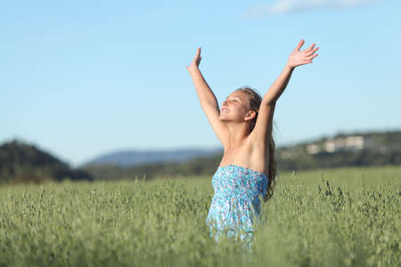 Woman with raised arms in a green meadow enjoying the wind with the blue sky in the background photo