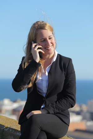 conversating: Close up of a happy businesswoman on the mobile phone with the sky in the background      Stock Photo