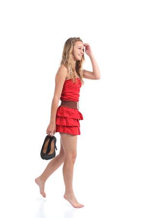 Muchacha adolescente hermosa que desgasta vestido que camina con tacones colgando de aislados en un fondo blanco la mano Foto de archivo - 20085485