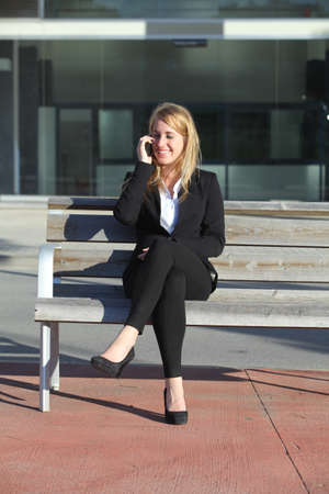 Businesswoman talking on the mobile phone sitting on a bench in front the office photo