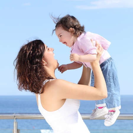 Pretty mum laughing and raising her baby girl with the sea in the background photo