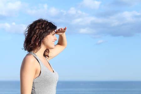 美しい女性の額に手とバック グラウンドで海を楽しみにして