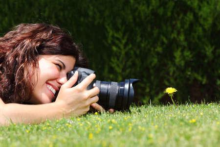 Profiel van een mooie vrouw die een macro fotografie van een bloem op het gras in een park Stockfoto