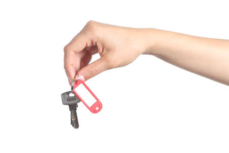 side keys: Side view of a woman hand giving a house keys isolated on a white background