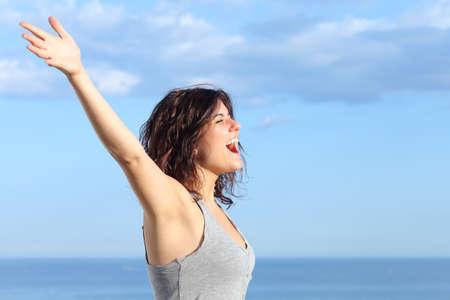 Aantrekkelijke vrouw met opgeheven armen schreeuwen naar de wind op het strand met de zee en de blauwe hemel op de achtergrond