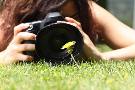 digicam: Close up of a pretty girl taking a photograph of a flower on the grass in a park Stock Photo