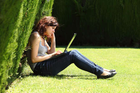 Attractive woman bored with a laptop sitting on the grass in a park with an unfocused dark background    Stock Photo - 20200932