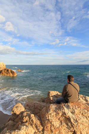 blue sky thinking: Man sitting on a rock in the beach and looking the sea in a beautiful landscape Stock Photo