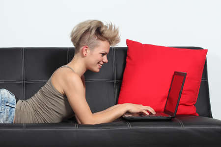 lying on side: Fashion woman browsing internet in a laptop at home lying on a black couch Stock Photo