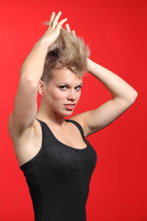 Fashion woman stretching her punk style hair on a red background photo