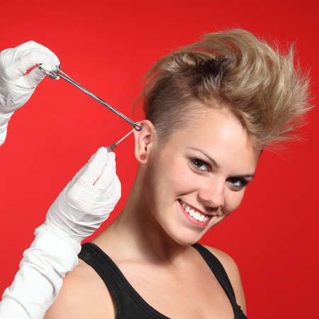 Professional hands making a piercing hole to a fashion woman on a red background