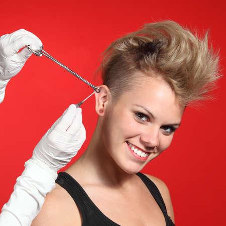 Professionele handen maken van een piercing gat om een mode vrouw op een rode achtergrond Stockfoto