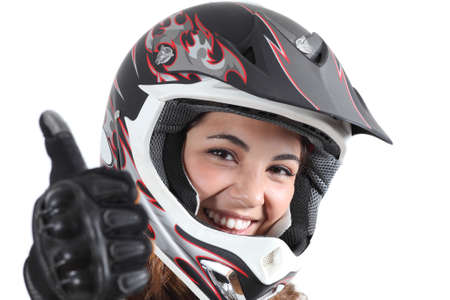 Happy biker woman with a motocross helmet and thumb up isolated on a white background Imagens