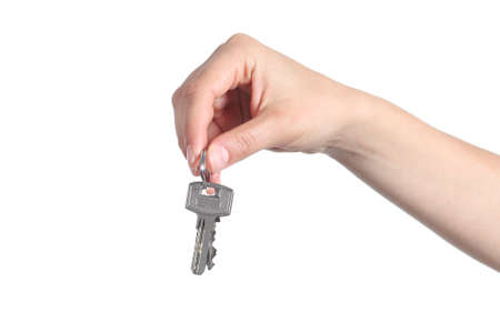 side keys: Side view of home keys hanging from a woman hand isolated on a white background