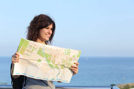 lost city: Beautiful tourist woman on vacation with a city map with the sea and sky in the background