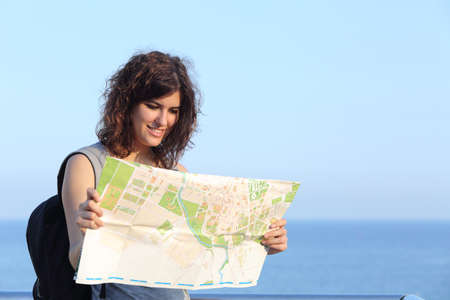 Beautiful tourist woman watching a city map with the sea and the sky in the background photo