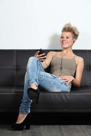 Fashion teenager listening to the music from a smartphone sitting on a couch at home                  photo
