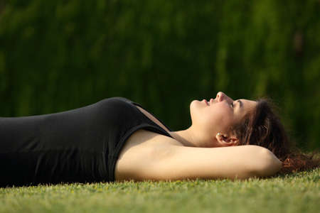 quiet adult: Attractive woman relaxed lying on the grass with a dark background Stock Photo