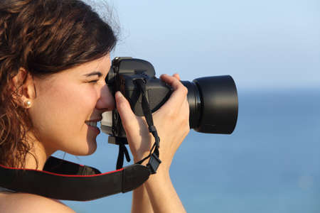 digicam: Attractive woman taking a photograph with her camera with the sea in the background Stock Photo