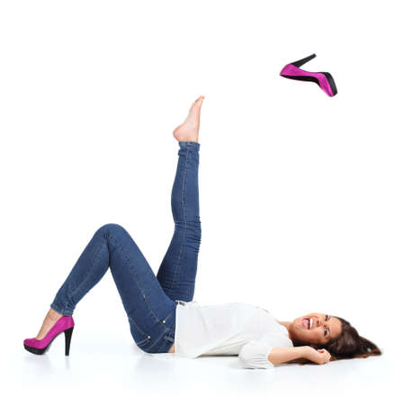 Aantrekkelijke vrouw met jeans het gooien van een fuchsia hak geïsoleerd op een witte achtergrond