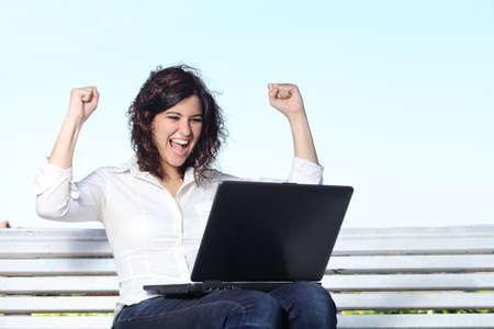 Empresaria Euphoric con un ordenador portátil sentado en un banco con el cielo en el fondo