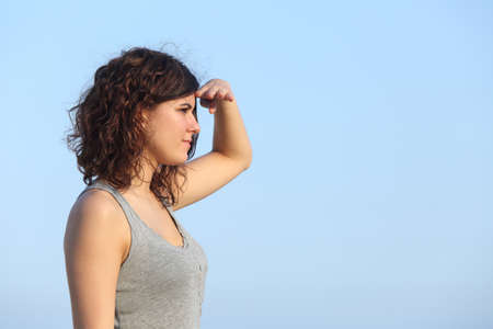 expectations: Attractive woman looking ahead with the hand in forehead with the blue sky in the background