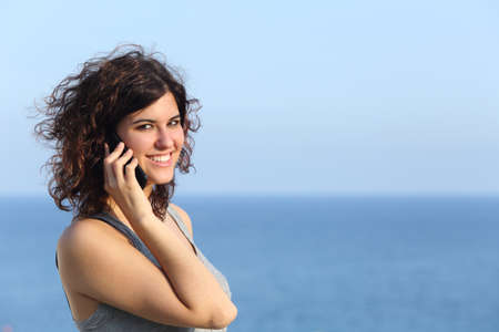 Attractive casual woman talking on the mobile phone with the sea in the background photo