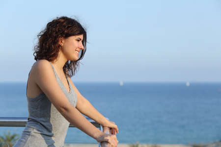Attractive woman looking ahead from a balcony with the sea in the background photo