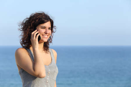 Beautiful woman talking on the mobile phone with the sea in the background photo