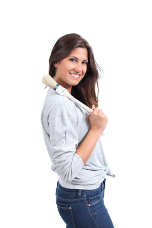 reforming: Beautiful woman smiling with a paintbrush ready to paint               Stock Photo