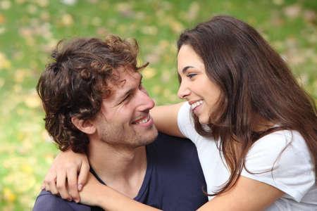 Paar knuffelen en flirten in een park met een groene ongericht achtergrond