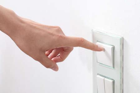 hands off: Mano de la mujer de encender la luz con un interruptor de pared