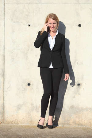 conversating: Businesswoman talking on the phone leaning on a concrete wall