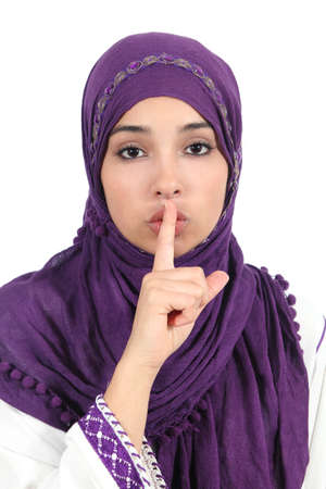 Beautiful islamic woman wearing a hijab asking for silence isolated on a white background photo