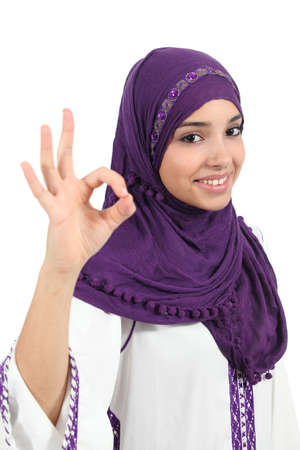 Beautiful happy muslim woman wearing a hijab gesturing ok isolated on a white background                 photo