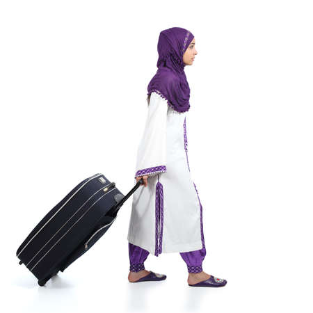 immigrant: Profile of a muslim immigrant woman wearing a hijab walking carrying a suitcase isolated on a white background                Stock Photo
