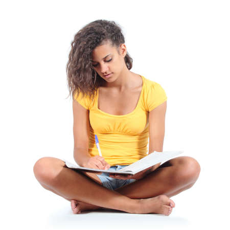 Teenager girl sitting and studying isolated on a white background               photo