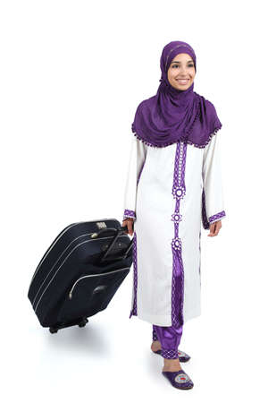 tourist destination: Arab traveler woman walking carrying a suitcase isolated on a white background             Stock Photo