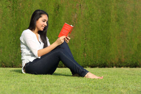 Beautiful arab woman reading a book sitting on the lawn of a park with a green background photo