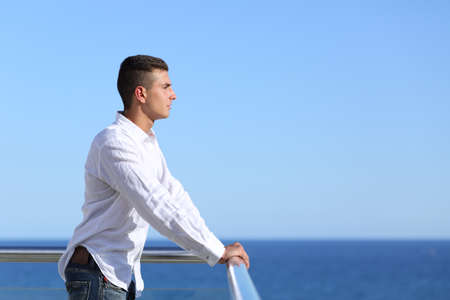banister: Handsome man looking at the horizon with the sea and a blue sky in the background