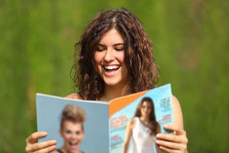 Gelukkige vrouw het lezen van een tijdschrift in een park met een groene achtergrond