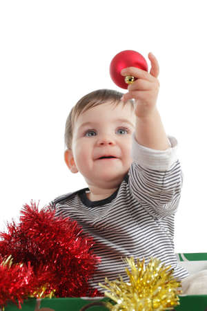holding a christmas ornament: Pretty baby girl holding a christmas ball isolated on a white background