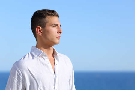 Handsome man looking at the horizon with a blue sky in the background                 photo