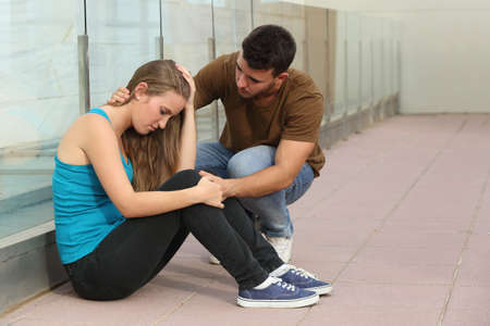 Beautiful teenager girl worried sitting on the floor and a boy comforting her