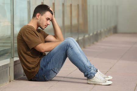 Teenager boy worried sitting on the floor with a hand on the head photo