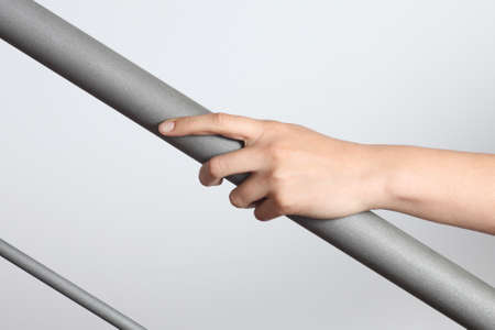 Woman hand using a railing to go upstairs with a light grey background photo